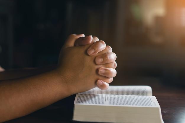 Mani cristiane mentre pregano e adorano per gesù. persone cristiane che pregano mentre le mani adorano su una bibbia. imparare la religione.
