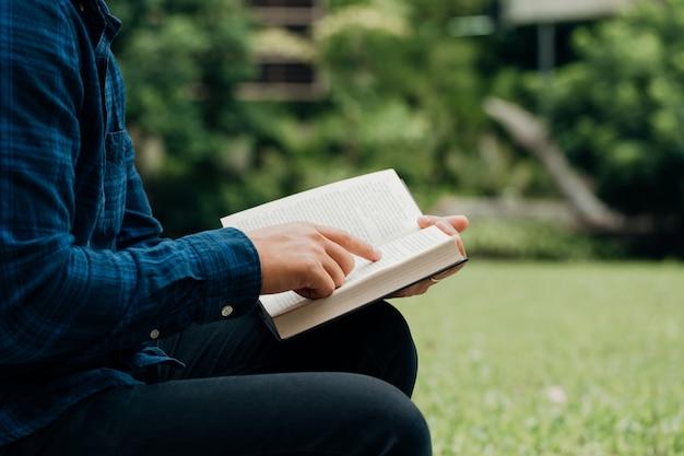 Concetto di studio della bibbia e dei cristiani. giovane uomo seduto a leggere la bibbia nello spazio garden.copy
