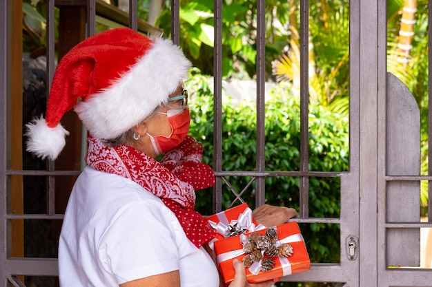 Natale 2020 con il coronavirus. una donna messaggera anziana che indossa un cappello da babbo natale e una maschera medica per evitare l'infezione da coronavirus che consegna regali di natale a casa