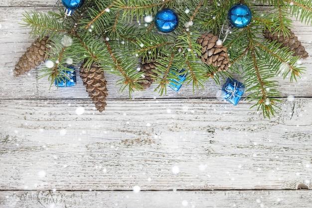 Accessori natalizi in blu, cono e rami di abete su fondo bianco in legno