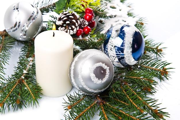 Accessori natalizi in blu e ramo di abete su bianco