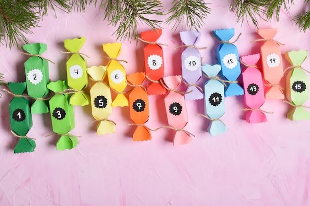 Christmas advent è un calendario realizzato con carta colorata, realizzato con le tue mani su uno sfondo rosa.