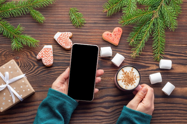 Ambiente natalizio con mockup di smartphone in mano di donna su tavolo di legno con rami di abete e dolci. concetto di acquisto online di capodanno.
