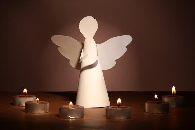 Angelo di natale con candele su sfondo scuro
