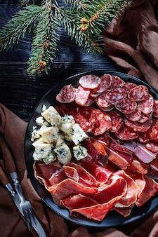 Antipasti di natale - formaggio, salsicce e salumi secchi - jamon, chorizo, formaggio a muffa blu, salsicce fuet a fette su un piatto su un tavolo con abete, vista dall'alto