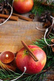 Disposizione natalizia di mele, rami di abete, spezie e candele.