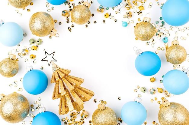 Disposizione di natale, cornice di palle di natale blu e oro su sfondo bianco. disposizione piatta, vista dall'alto