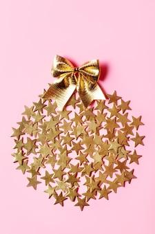 Disposizione di natale con stelle dorate e fiocco sulla superficie rosa
