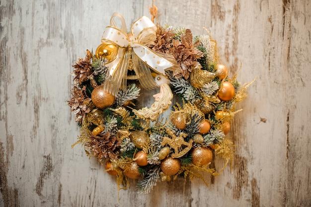 Ghirlanda artificiale di natale con ornamenti dorati, palline, nastri e fiori luccicanti