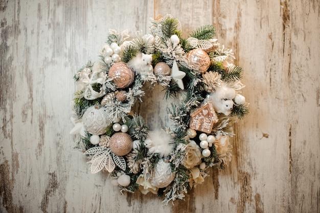 Corona artificiale di natale con ornamenti, palline, nastri e fiori di colore bianco e rosa