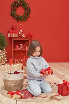 Neonata di natale con i regali vicino all'albero di natale