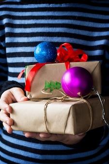 Sfondo di natale un bambino che fa un regalo di natale con un nastro rosso e palline decorative
