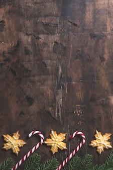 Sfondo di natale. composizione in natale con rami di abete, regali, dolci, biscotti, cannella su uno sfondo di legno scuro