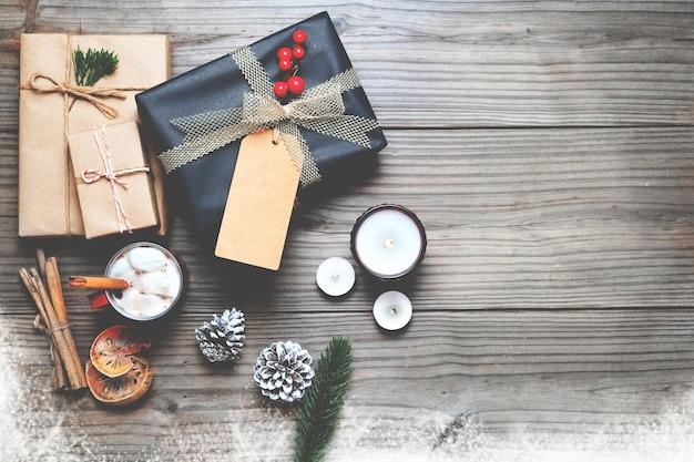 Sfondo natale - regalo di natale regali di natale e decorazione rustica su sfondo di legno vintage con fiocco di neve. layout piatto creativo e composizione di visualizzazione superiore con disegno di confine e copia.