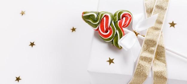 Sfondo di natale, scatola regalo rossa regalo di natale ed elementi decorativi su sfondo bianco. creativo festivo flat lay e composizione vista dall'alto copia design dello spazio.