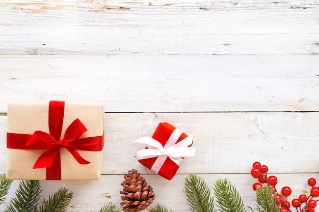 Natale sfondo - regalo di natale regalo rosso scatola e elementi decorativi su sfondo bianco di legno. layout piatto creativo e composizione di visualizzazione superiore con disegno di confine e copia.