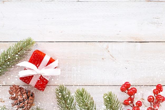 Sfondo natale - regalo di natale regalo rosso scatola e decorazione elementi su fondo bianco di legno con fiocco di neve. layout piatto creativo e composizione di visualizzazione superiore con disegno di confine e copia.