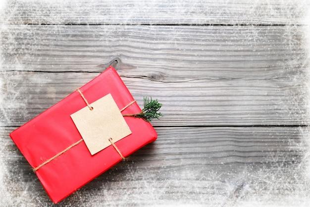 Natale sfondo - regalo di natale regalo rosso casella su sfondo di legno vintage con fiocco di neve. layout piatto creativo e composizione di visualizzazione superiore con disegno di confine e copia.