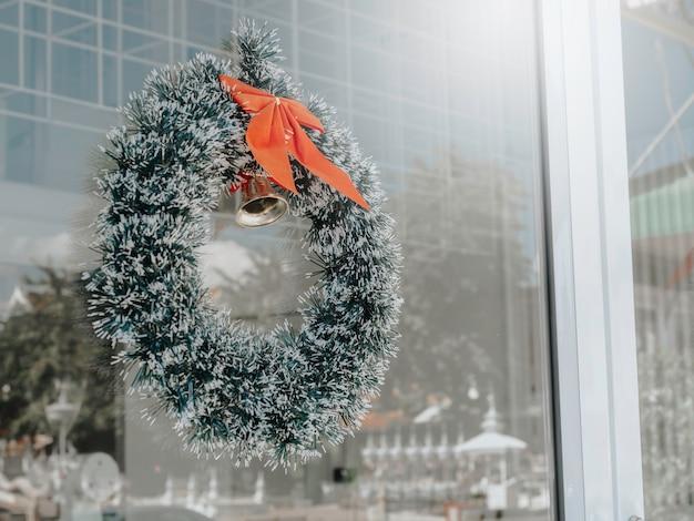 Sfondo di natale. corona di natale decorata con nastro rosso e una campana d'oro appesa a una porta di vetro pulita di fronte al caffè.