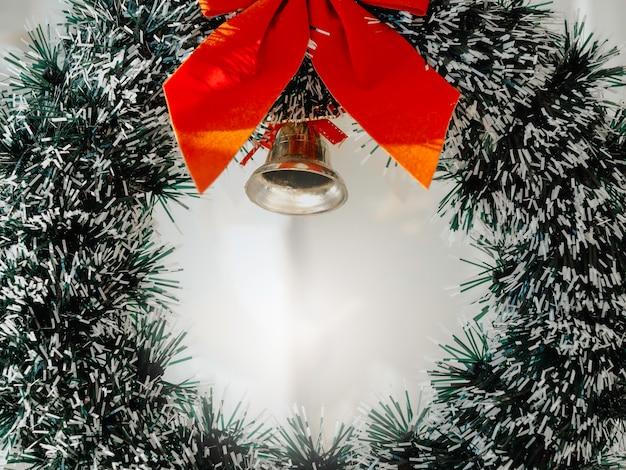 Sfondo di natale. close-up ghirlanda di natale ornata con nastro rosso e una campana d'oro appesa su una porta di vetro pulita di fronte al caffè.