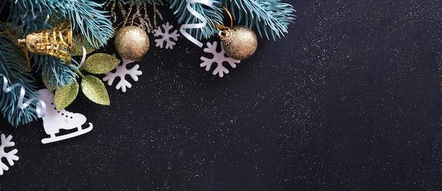 Sfondo di natale decorato con rami di albero, fiocchi di neve, campane e pattini con spazio di copia.