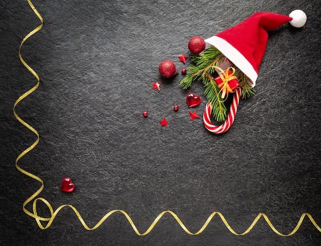 Sfondo di natale ramo di abete decorazioni natalizie regalo di canna al caramello in un cappello di babbo natale