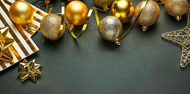 Sfondo di natale da palline d'oro, serpentine su uno sfondo scuro. biglietto natalizio. copia spazio.