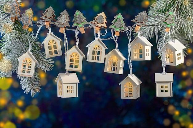 Sfondo di natale di una ghirlanda di luci a forma di case su rami di abete innevati
