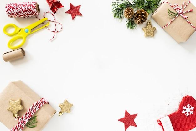 Contenitore di regalo del fondo di natale con la stella e le pigne rosse su fondo bianco.
