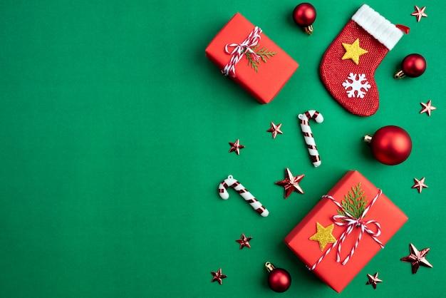 Fondo di natale, contenitore di regalo con la decorazione dei calzini su fondo verde.