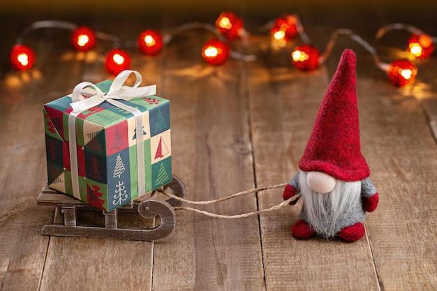 Sfondo di natale. gnomo in berretto rosso è sulla slitta che trasporta una scatola di regali di festa