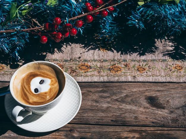 Sfondo di natale. caffè caldo in una tazza bianca su tavola di legno decorazione con ornamento di natale, vista dall'alto con spazio copia.