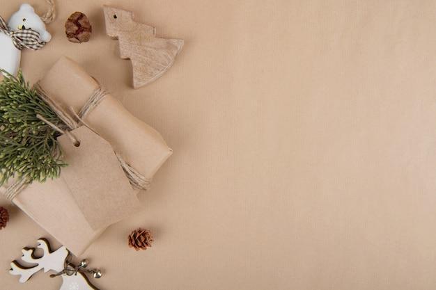 Sfondo di natale, rami di abete naturale con giocattoli di legno e regalo artigianale su un fondo di legno bianco, vista dall'alto di banner web orizzontale di nuovo anno