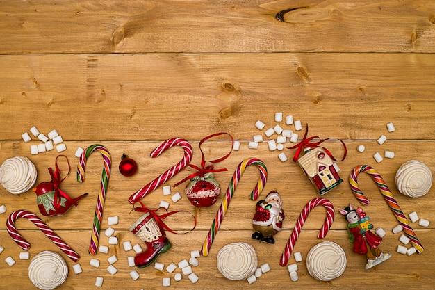 Natale sfondo rosso natale giocattoli a strisce lecca-lecca e marshmallow su tavole di legno scuro
