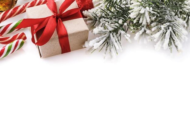 Sfondo di natale su sfondo bianco con caramelle regalo e ramo di abete rosso