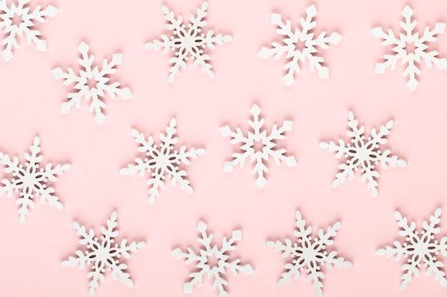 Sfondo di natale. decorazioni bianche della neve su fondo rosa.