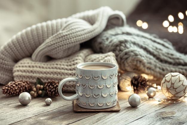 Sfondo di natale con una bella tazza, elemento a maglia e dettagli decorativi su uno sfondo sfocato con bokeh.