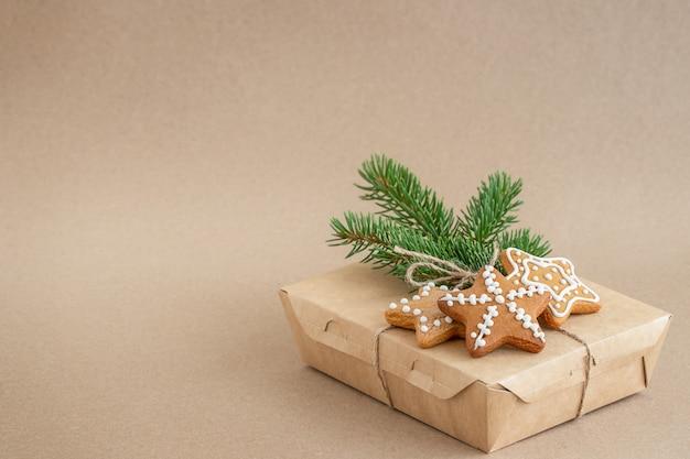 Sfondo di natale con una scatola di biscotti di pan di zenzero e un ramo di un albero di natale