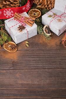 Sfondo di natale con decorazioni e scatole regalo su tavola di legno scuro.