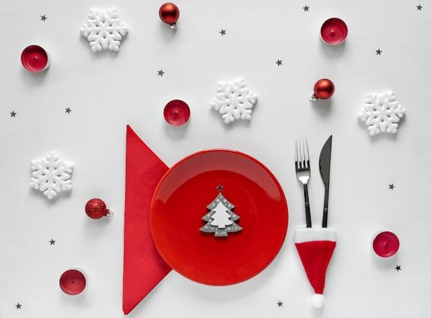 Sfondo di natale con piatto vuoto. apparecchiature in tavola con forchetta e coltello, addobbi per la tavola di capodanno. vista piana, vista dall'alto