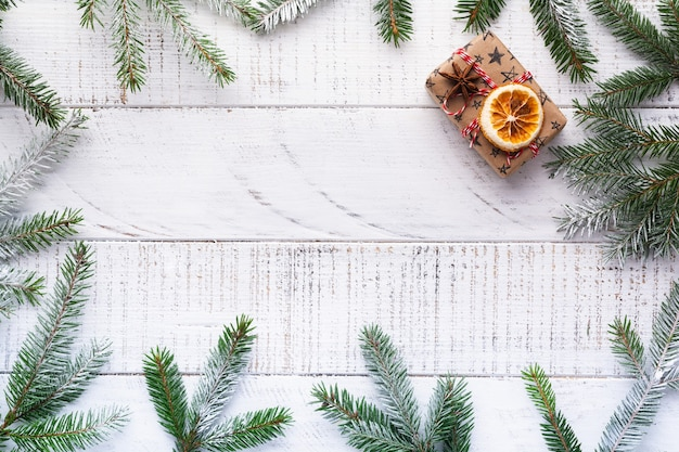 Sfondo di natale con rami di abete, pigne nelle quali, confezione regalo, arance secche, anice stellato e bacche sulla vecchia tavola di legno bianca. vista dall'alto.