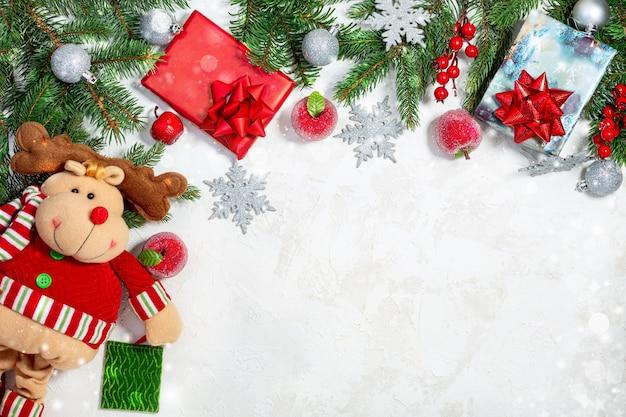 Sfondo di natale con rami di abete, palline d'argento, mele rosse, fiocchi di neve, scatole regalo e un divertente cervo
