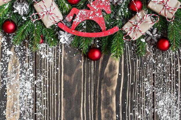 Sfondo di natale con rami di abete, scatole regalo, decorazioni e pigne