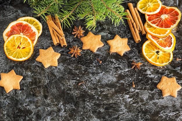 Sfondo di natale con abete arancio secco e cannella anice e stella di biscotti di panpepato su sfondo scuro con copyspace