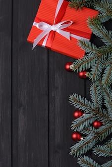Sfondo di natale con albero di abete e confezione regalo su tavola di legno nero