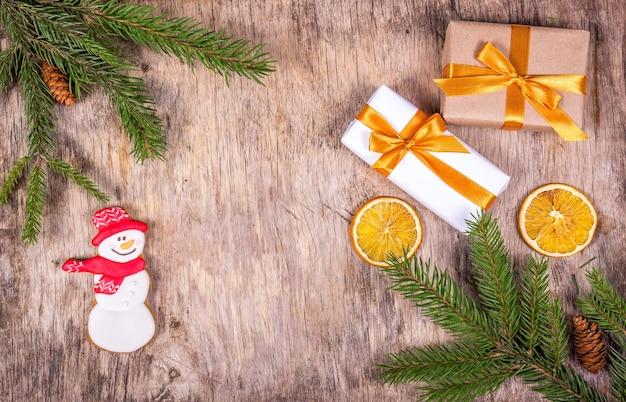 Sfondo di natale con albero di abete, scatole regalo e pupazzo di neve di pan di zenzero