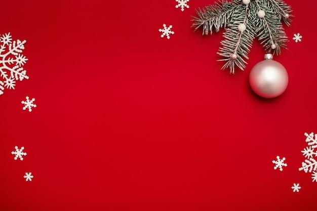 Sfondo di natale con abete, palla bianca e fiocchi di neve su rosso.