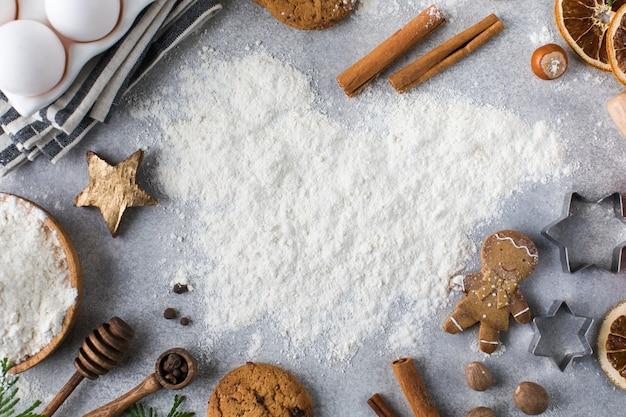 Sfondo di natale con farina su sfondo grigio circondato da mattarello di spezie e biscotti
