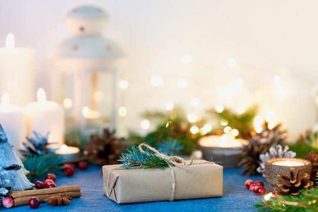 Sfondo di natale con confezione regalo e decorazioni, candele e ghirlande di luci.