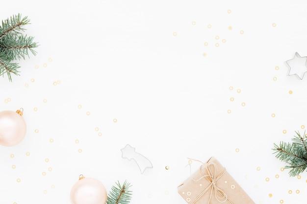 Sfondo di natale con scatola regalo, abete verde, decorazioni su bianco